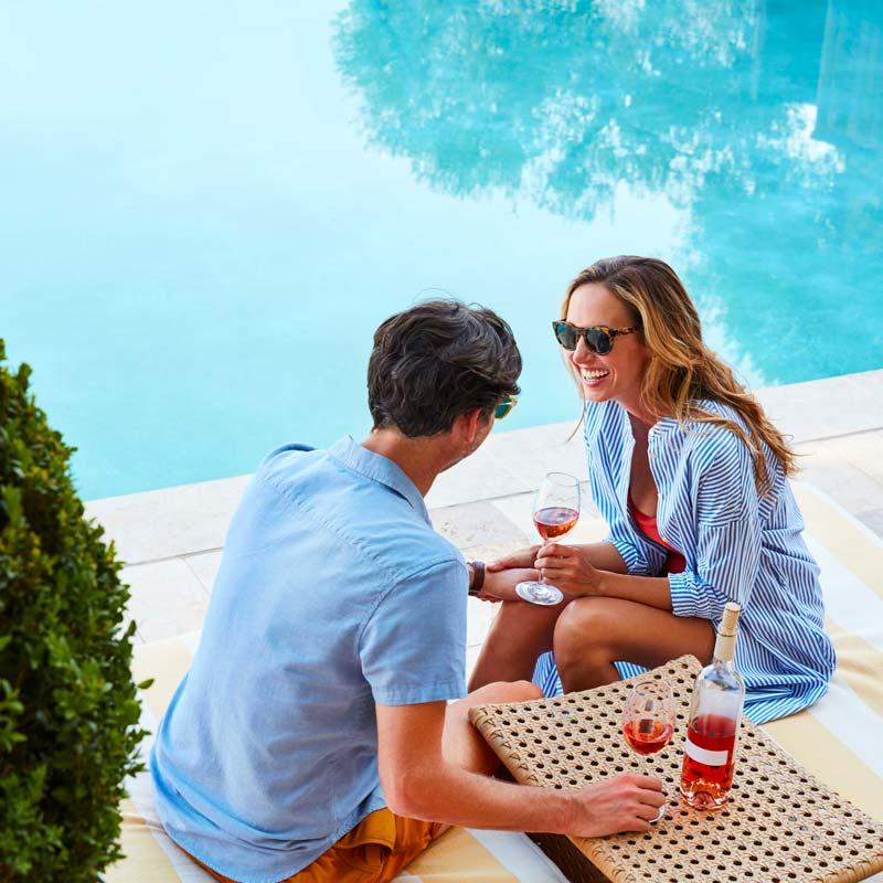 couple drinking wine near a resort pool