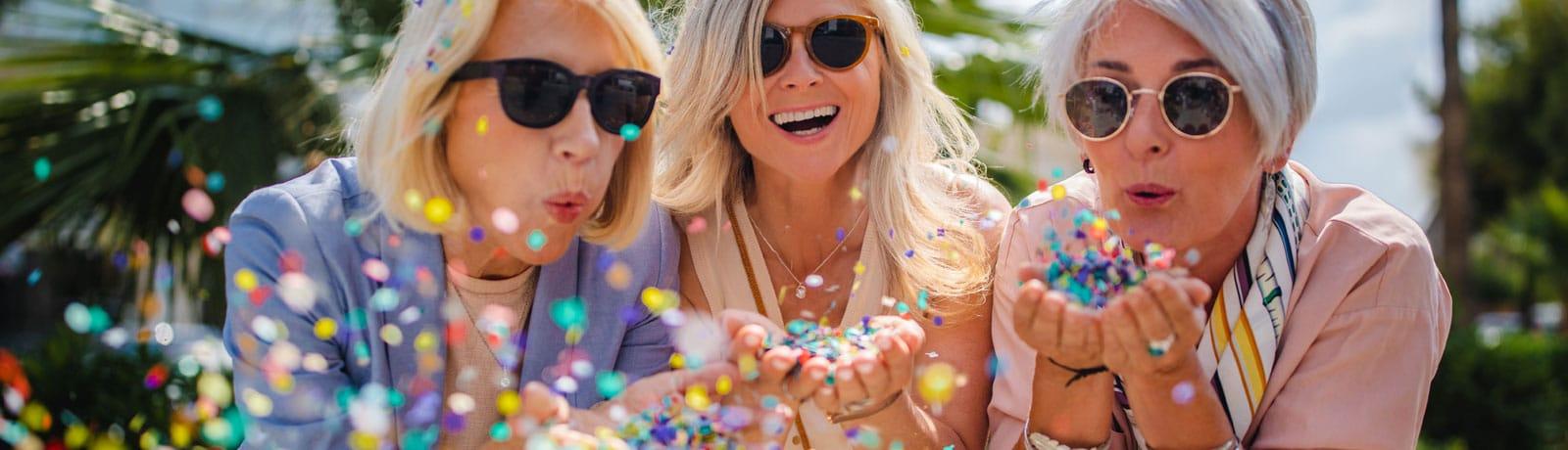 three women blowing confetti