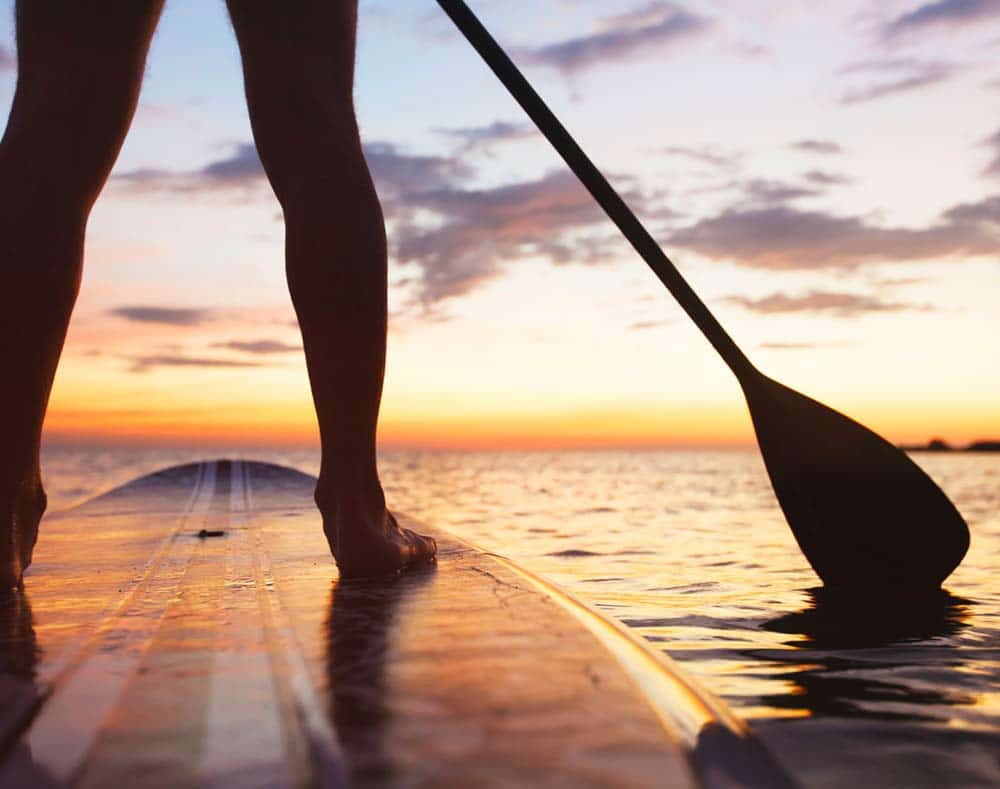 paddleboarding with sunset view on the water