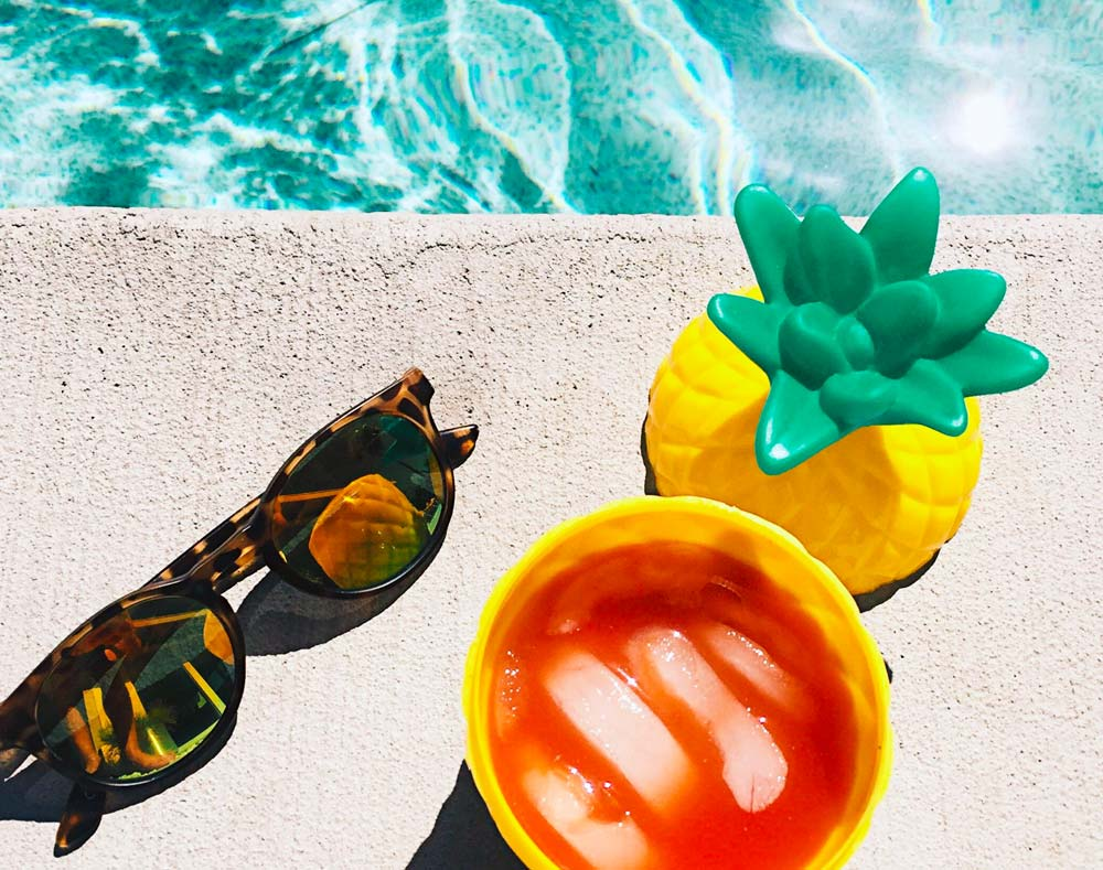 sunglasses with drink by the pool