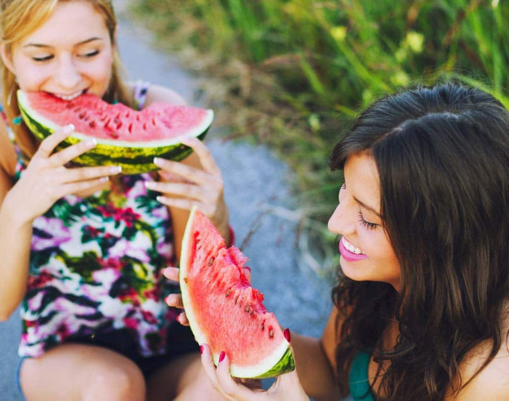 two people eating watermelon