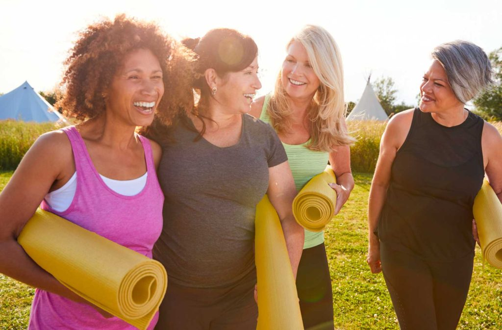 four women with yoga mats laughing