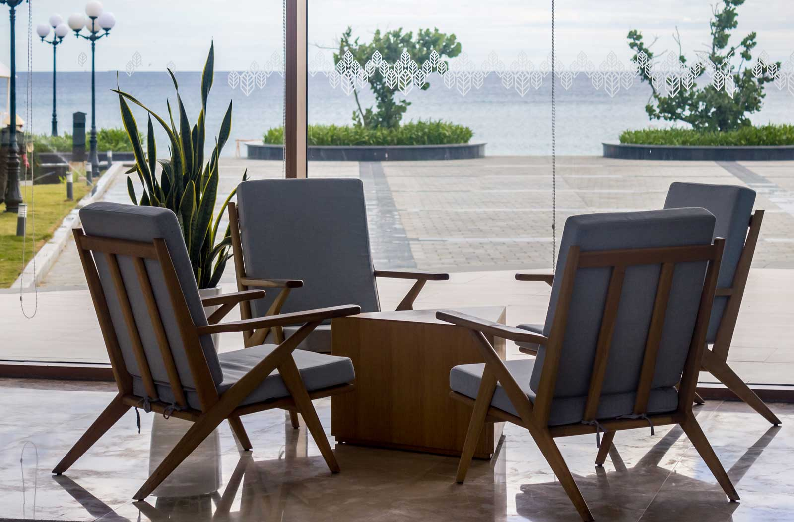 four chairs in lobby of hotel overlooking water
