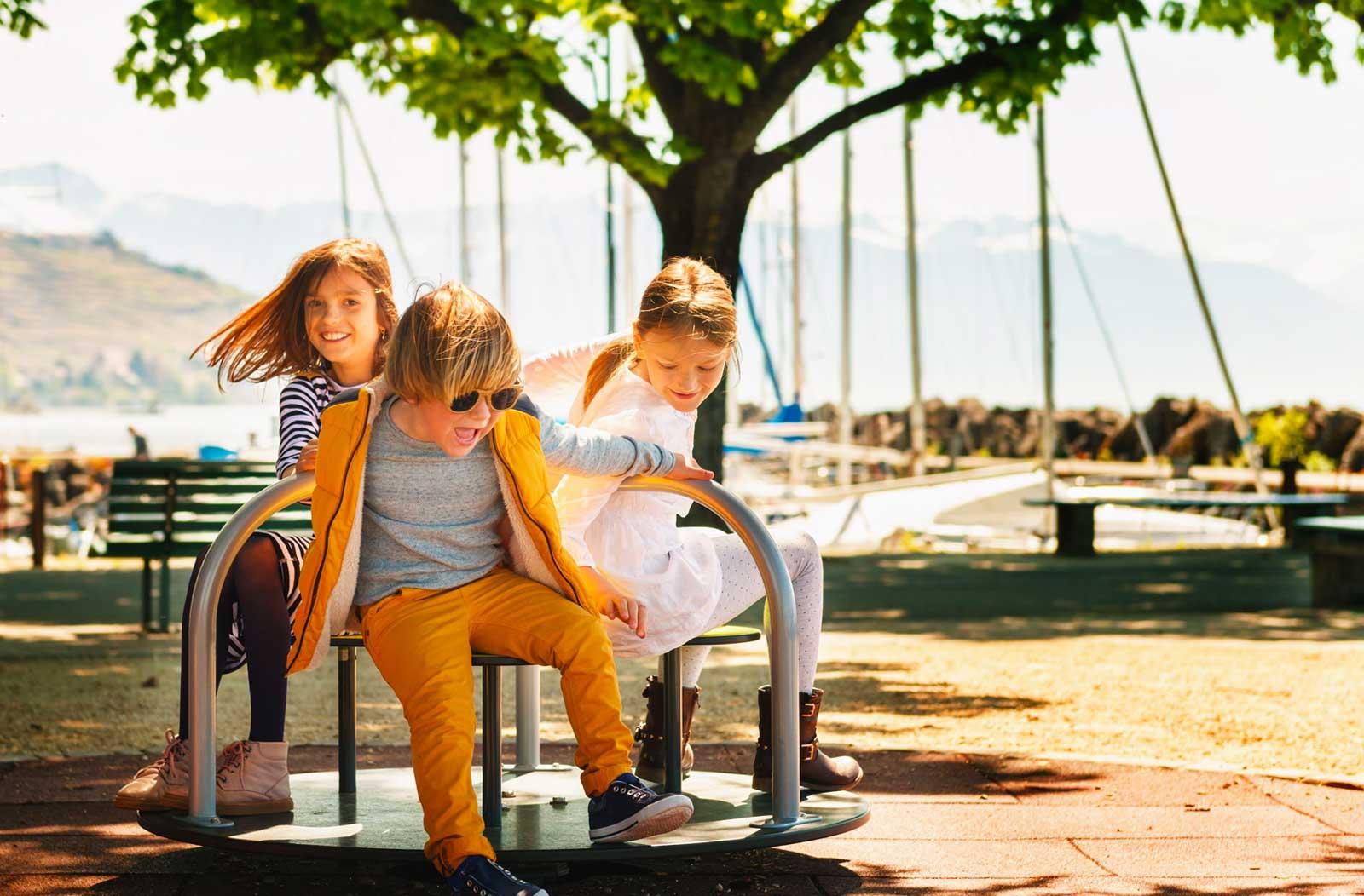 three kids playing on a playground